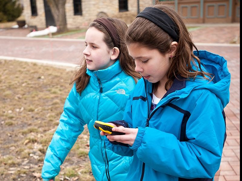 two girls with geocache units outdoors